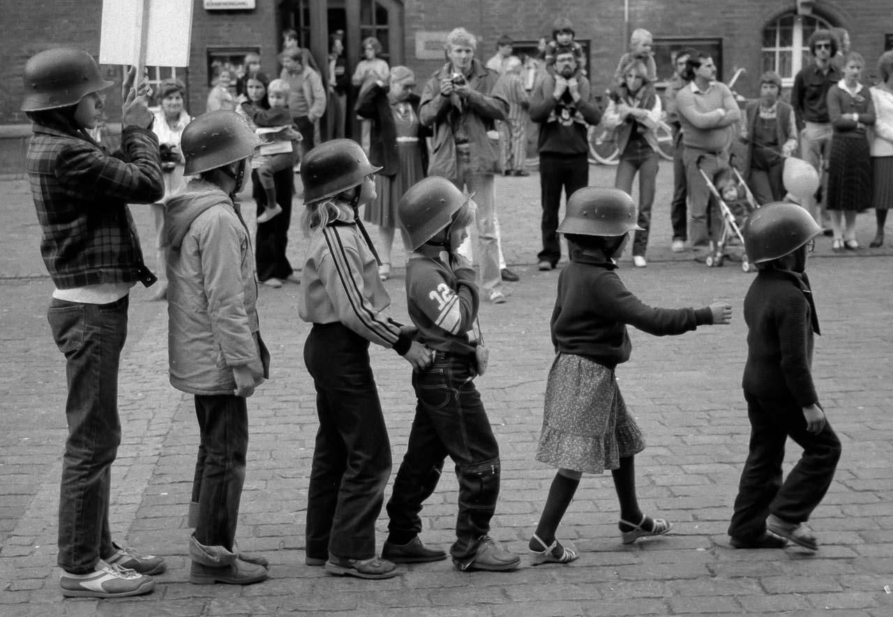 Der Anachronistische Zug war ein politisches Straßentheater, das auf dem 1947 entstandenen gleichnamigen Gedicht von Bertolt Brecht basierte. Der Straßentheaterzug formierte sich 1980 in München als Protest gegen den damaligen Kanzlerkandidaten der CDU/CSU, Franz Josef Strauß, und präsentierte sich in mehreren deutschen Städten. Im September 1980 erreichte der Zug den Rathausmarkt in Kiel, wo dieses Szenenfoto entstand. © Holger Rüdel