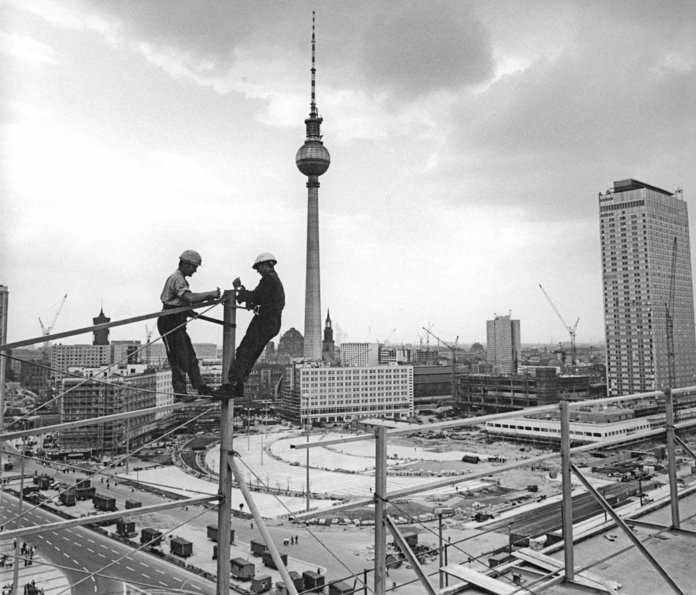 """Bauarbeiter bei Montagearbeiten an der Leuchtschrift auf dem """"Haus der Statistik"""", 13. August 1969 © Bundesarchiv   Foto: Eva Brüggmann"""
